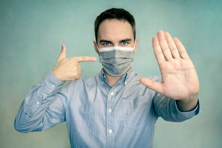 Mandatory wearing of a mask in a public place. Warning. Portrait of serious man show stop sign gesture warn people stay home wear medical over bright color background