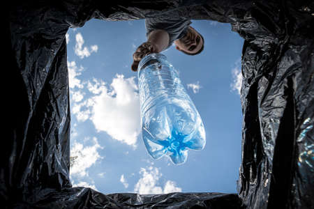 a man throws empty plastic bottle into a trash can. Bottom view from the trash can. The problem of recycling and pollution of the planet with garbage. 免版税图像