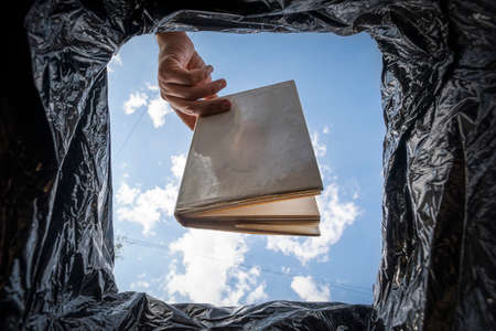 Book that do not read, low-grade literature. A stupid, uneducated man throws his textbook in the trash. The concept of bad education. Digitalization and e-books. Unnecessary reading.