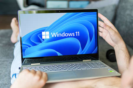 Windows 11 logo on laptop screen. A new operating system update from Microsoft