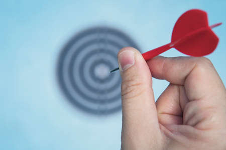 Business education success and target concept. Close up a hand is targeting the green dart arrow towards the center of dartboard. hit the target. Success in business. Banque d'images