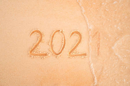 Years 2021 are inscribed on sandy beach on the yellow sand close-up. The sea wave washes away the inscription 2021. The concept of year change.