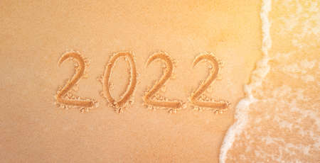 2022 figures on sandy beach in the background New Year's Eve. The sea wave washes away the inscription 2022 on the yellow sand close-up. New year holidays on the beach.