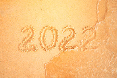 2022 written in sand, on tropical beach. The concept of year change. sea wave washes away the inscription. Celebration of new year holidays in warm countries. Фото со стока