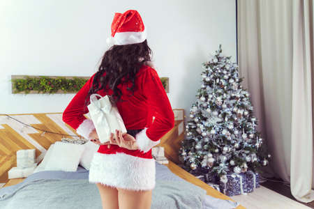 Close up shot of young woman hiding present for her boyfriend behind back. Surprising white gift box with white ribbon. Christmas and New Year or Happy birthday concept. Home cozy atmosphere