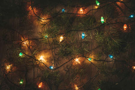 Christmas colorful lights and the green branches of the Christmas tree on wooden table