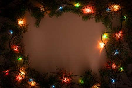 Christmas lights frame on dark background. Holiday shiny garland border top view. Xmas tree decorations, winter holidays illumination Фото со стока