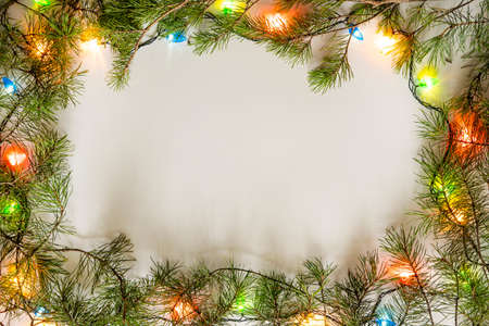 Bright Christmas frame of spruce, christmas decorations on white background. Copy space. Winter holidays, New Year.