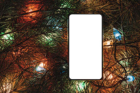 Smartphone surrounded by Christmas tree and accessories. Smartphone surrounded by fir branches. Blank screen for design or text. Christmas decorations and technology concept.