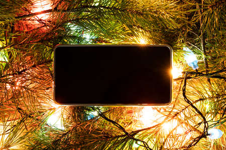 Smartphone surrounded by fir branches. Blank screen for design or text. Christmas decorations and technology concept.