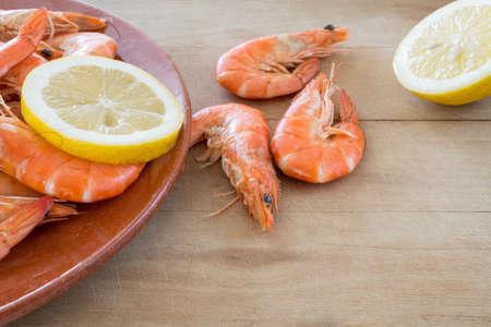 arranged: boiled shrimp with lemon arranged on kitchen board