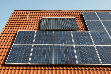 赤い屋根の上のソーラー パネル 写真素材