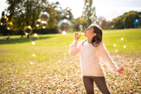 Adorable little girl outdoors at beautiful autumn day blows soap bubbles