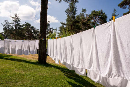 laundry line: fresh clean white towels drying on washing line in outdoor
