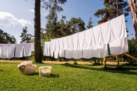 frisse, schone witte handdoeken te drogen op waslijn in de buitenlucht