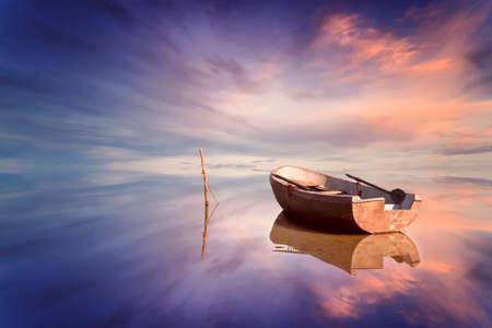 cielo y mar: Barco solo y puesta de sol incre�ble en el mar Foto de archivo
