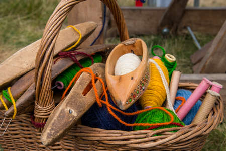 basket weaving: weaving shuttles and  multi-colored yarn in a basket Stock Photo
