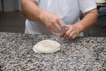 kneading: close up of female hands kneading dough and making banitsa - typical bulgarian pastry Stock Photo