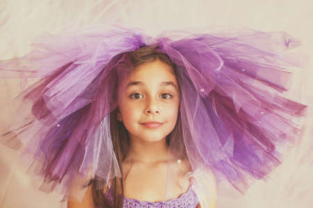 ballerina costume: Girl wearing purple dress  with a funny hat  and playful expression Stock Photo