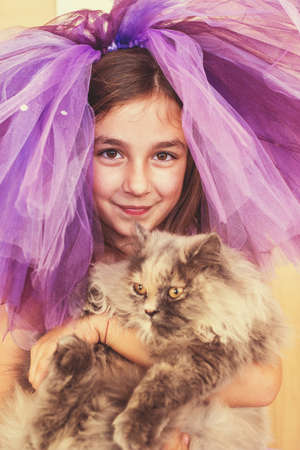 animal tutu: Girl dressed in purple with a funny hat holding a cat in her hands