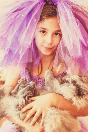 mignonne petite fille: Girl dressed in purple with a funny hat holding a cat in her hands