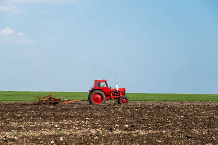 plough machine: red tractor in the agricultural field
