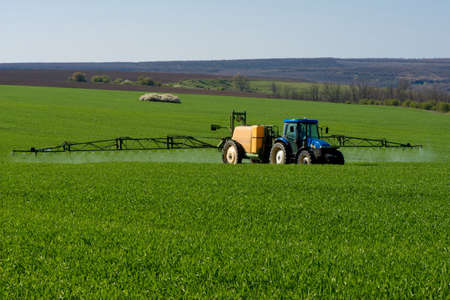 pesticide: Tractor spraying pesticide in a field of wheat - copy space