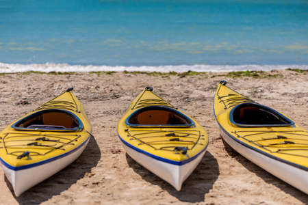 Colorful kayaks align the water - selective focus, copy space Stock Photo
