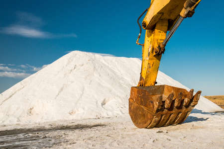 salt production - pile of salt and excavator at saltworks - selective focus, copy space