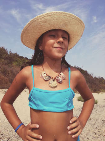little girl in a bathing suit on the beach wears a necklace of shells - selective focus