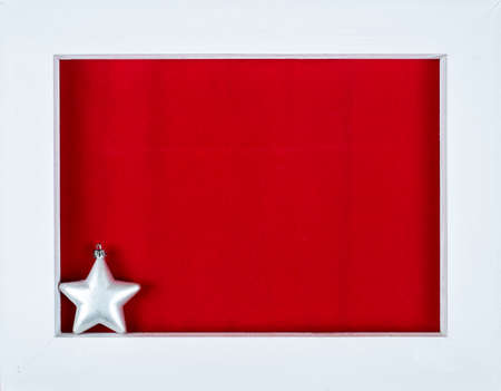 White wooden frame and astar over a red background - copy space