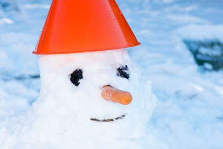 palle di neve: Piccolo pupazzo di neve in un cappuccio sulla neve in inverno - messa a fuoco selettiva, copia spazio Archivio Fotografico