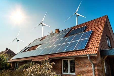 집과 바람 터빈 arround- 지속 가능한 자원의 개념의 지붕에 태양 전지 패널