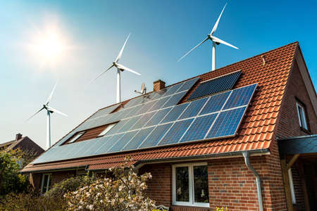 Zonnepaneel op een dak van een huis en wind turbins rond - concept van duurzame middelen Stockfoto