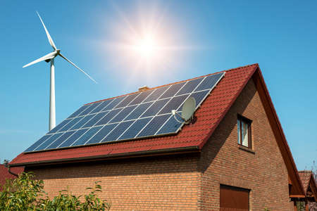 Solar panel on a roof of a house and wind turbins arround - concept of sustainable resources Stock Photo
