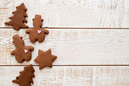 Christmas gingerbread cookies with different shapes over a white vintage wooden table