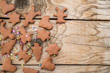 Christmas gingerbread cookies with different shapes over a vintage wooden table