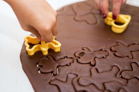 Childrens and womans hand makeing Christmas Gingerbread Cookies - selective focus
