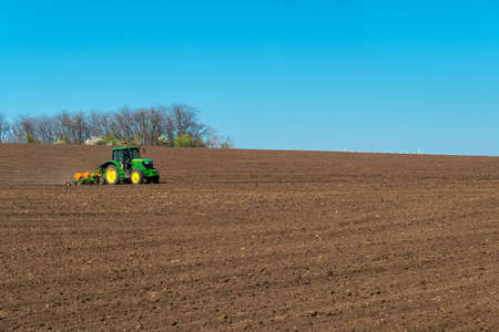Farmer with tractor seeding - sowing crops at agricultural fields in spring. Selective focus, copy space. Stock Photo