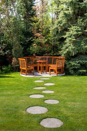 木製のテーブルとベンチを備えた春の庭で晴れた日 - ライフスタイルとレジャーの概念