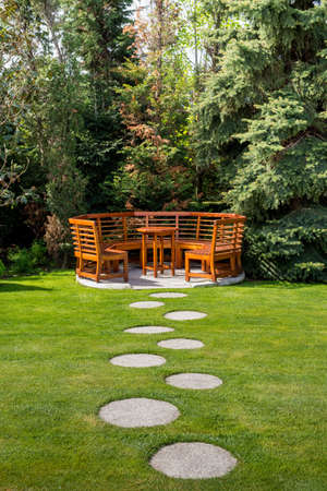 Sunny day in a spring garden with wooden table and benches - concept of lifestyle and leisure 免版税图像 - 90782892