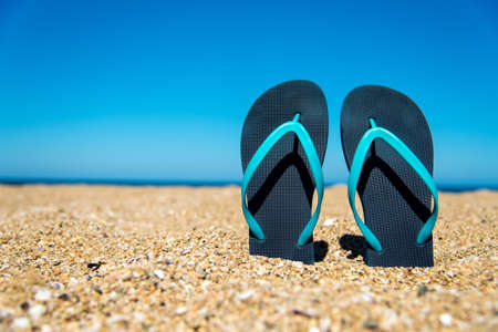 blue flip-flops on the sand - a concept for summer vacation, travel and leisure - selective focus, copy space Stock Photo