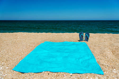Blue sandal flip flop and towel on yellow sand. Summer fun time and accessories on the beach, summer vacations, copy space.