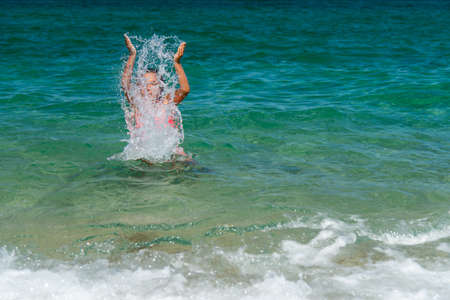 Girl having fun bathing in to the sea and splashing water - vacation concept, copy space Stock Photo