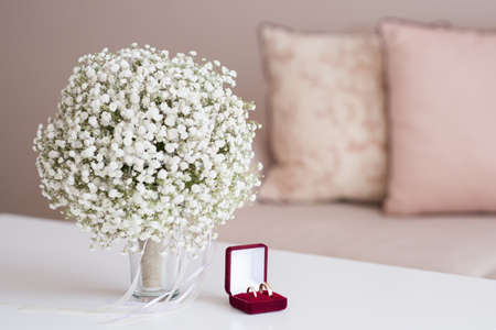 Wedding rings in a red velvet box and bridal bouquet over a white table - selective focus, copy space