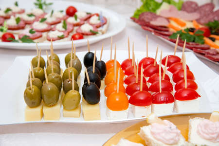 Close up of small canapes arranged on a plate over light background - selective focus 写真素材