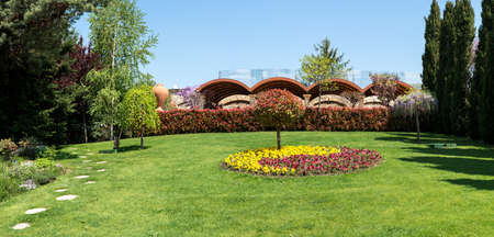 View of an attractive backyard with blooming flowers, conifers and well-kept lawns - wide angle view Stock Photo