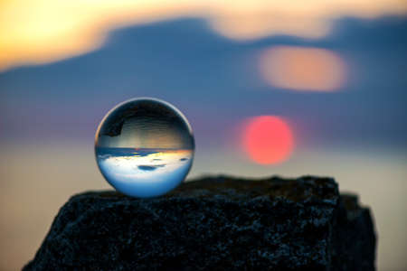 Upside down sunset landscape at Cape Kaliakra, Bulgaria, Eastern Europe - reflection in a lensball - selective focus, space for text Stock Photo