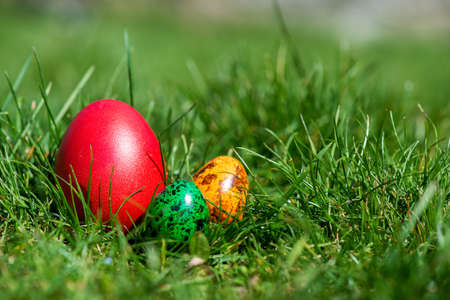Easter background with colorful eggs over fresh green grass - copy space Stock Photo