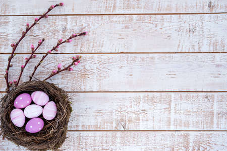 Easter background with colorful eggs in a nest over white wooden rustic table - copy space